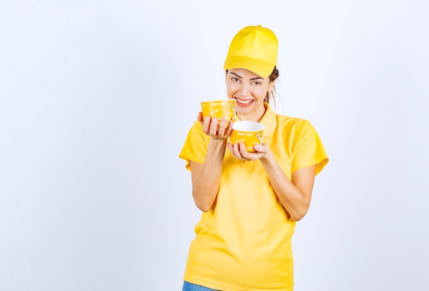 2つの持ち帰り用ヌードルカップを保持している黄色の制服を着た女性の女の子。