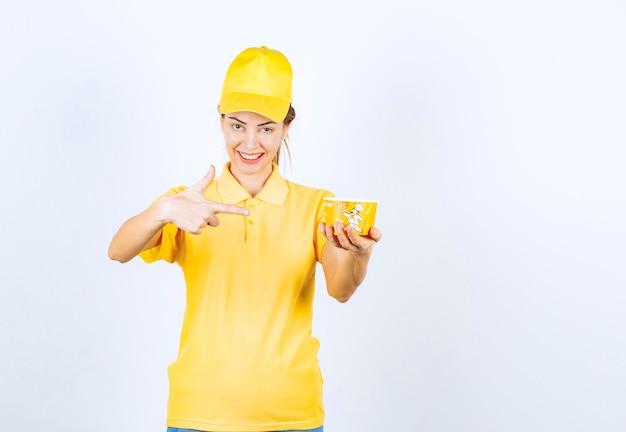 Ragazza femminile in uniforme gialla che consegna una tazza di noodle da asporto gialla al cliente.