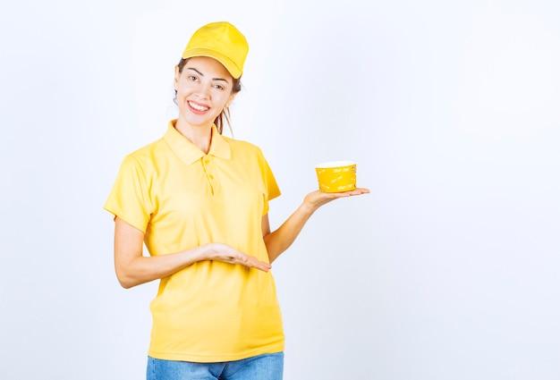 Ragazza femminile in uniforme gialla che tiene una tazza di noodle da asporto gialla.