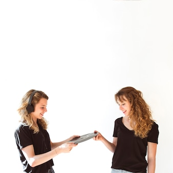 Female giving vinyl record to her sister wearing headphone over white backdrop