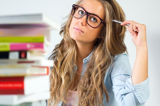 Female in glasses thinking holding pen