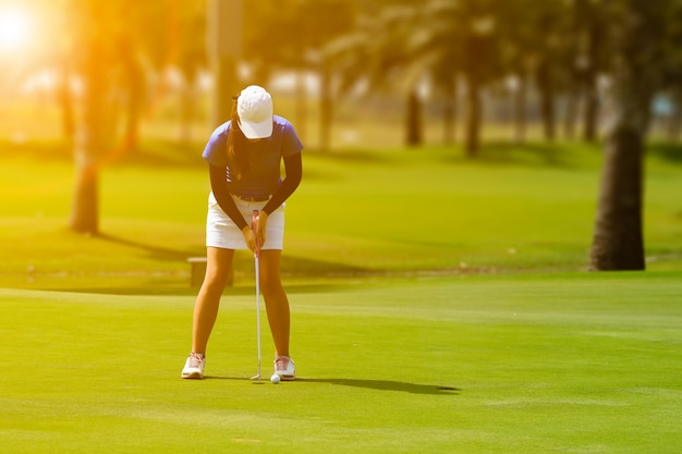 Female golf player putting golf on green during sunset with flare