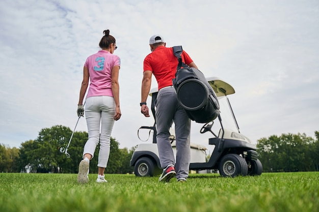Female golfer and her male instructor going toward a golf car