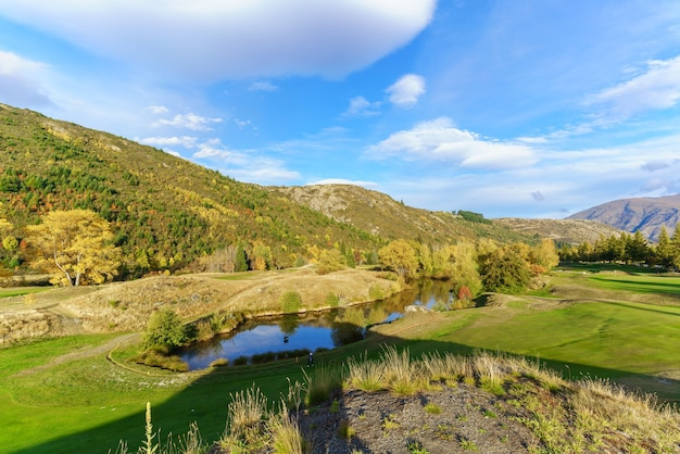 Female golfer is playing on arrowtown golf course in autumn , south island of new zealand