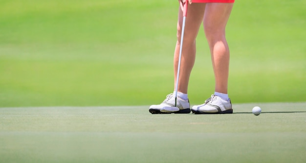 Female golfer putting on green.