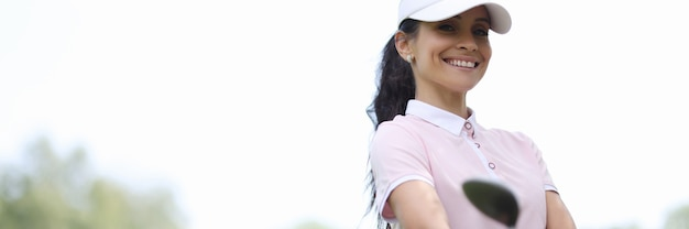 Female golfer smiles and holds bag of golf clubs