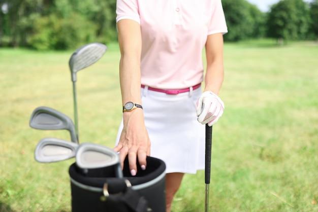 Female golfer stands next to golf bag