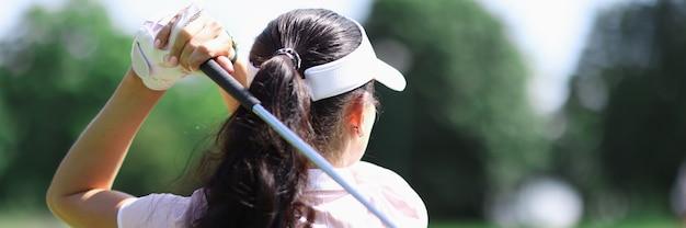 女性ゴルファーは仰向けに立ち、ゴルフクラブを手に持っています。