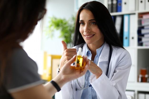 大麻濃縮油の患者スポイト瓶を与える女性gp