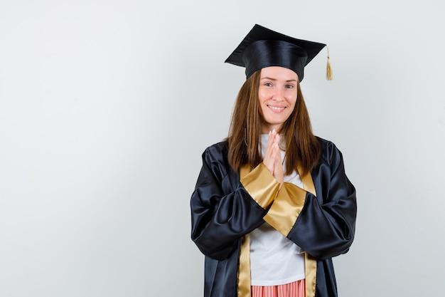 Laureato femminile in abito accademico mantenendo le mani nel gesto di preghiera e guardando allegro, vista frontale.