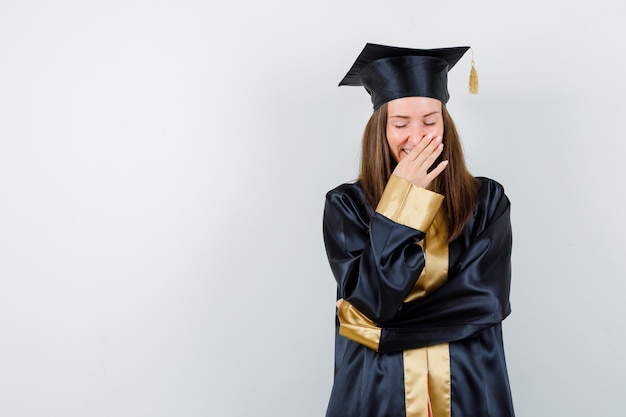 アカデミックドレスを着た女性の卒業生が口に手を当てて陽気に見える、正面図。