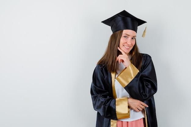 Выпускница-женщина в академической одежде подпирает подбородок пальцем и выглядит веселой, вид спереди.