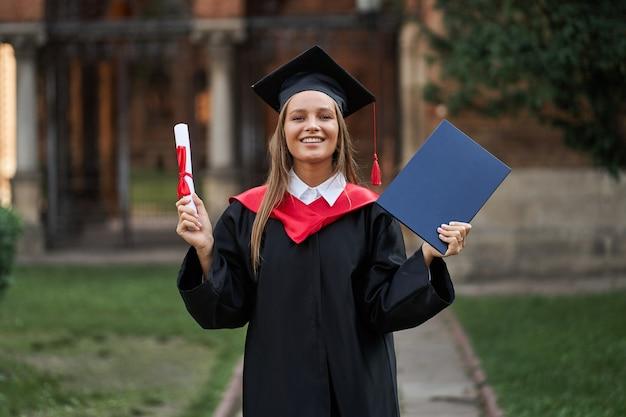 Выпускница в выпускном халате с дипломом в руках в кампусе.