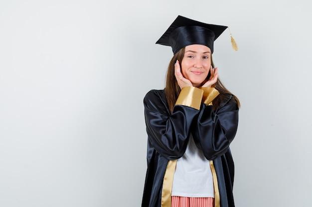 女性は制服を着たカジュアルな服を着て卒業し、顔の周りに手を保ち、平和な正面図を見せます。