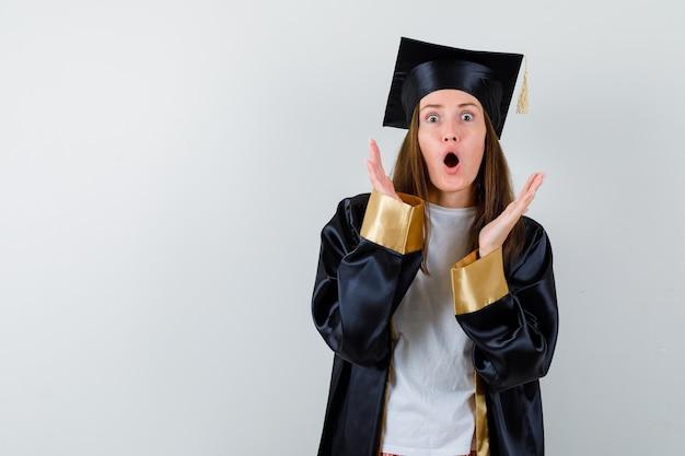 유니폼, 캐주얼 옷을 입은 여성 졸업생은 얼굴 가까이에 손을 유지하고 입을 열고 충격을받은 정면보기를보고 있습니다.