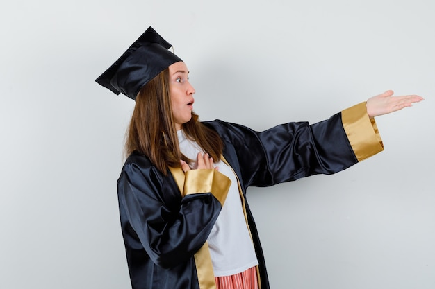 胸に手を当て、アカデミックドレスを着て手を伸ばし、驚いた女性卒業生。正面図。