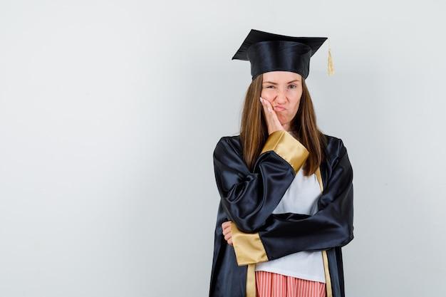 Laureato femminile che si appoggia sulla guancia sul palmo, labbra curve in uniforme, abbigliamento casual e che sembra insoddisfatto vista frontale.