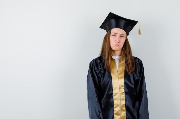カメラを見て、唇を曲げ、アカデミックドレスで顔をしかめ、悲しそうに見える女性卒業生。正面図。