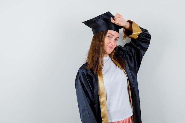 制服を着たカジュアルな服装で頭を抱えてポーズをとる女性卒業生。正面図。