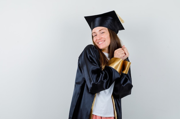 制服を着たカジュアルな服装で手を合わせてポーズをとる女性卒業生、陽気に見える正面図。