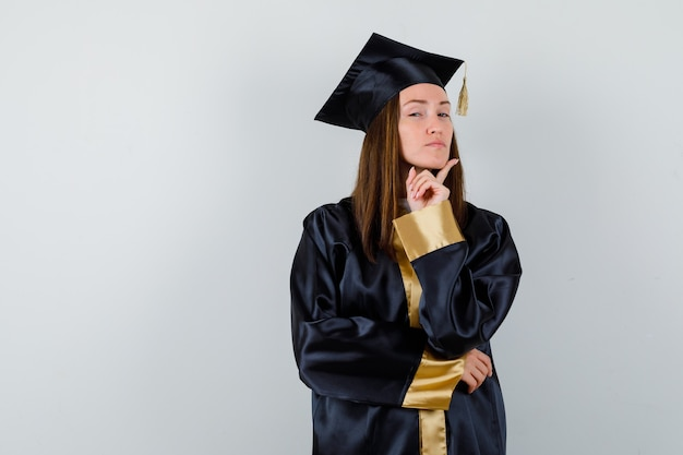 Female graduate propping chin on finger in academic dress and looking proud , front view.