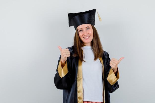 ガウン、カジュアルな服装で二重の親指を示し、幸せそうに見える女性の卒業生。正面図。