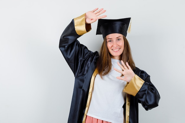 制服を着たカジュアルな服装でストップジェスチャーを見せ、陽気に見える女性卒業生。正面図。
