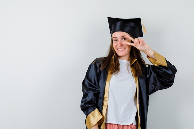 Female graduate showing v-sign near eye in academic dress and looking merry , front view.
