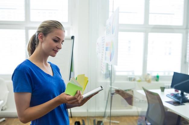 색상 견본 및 디지털 태블릿을 들고 여성 그래픽 디자이너