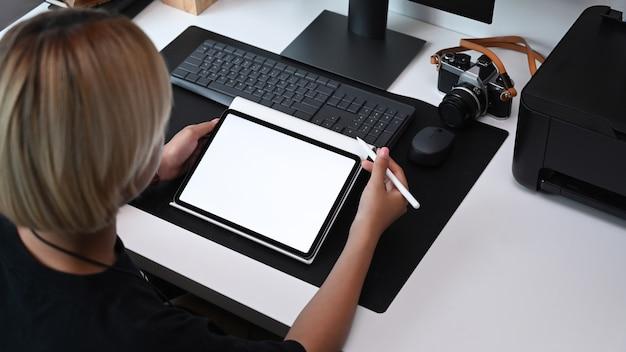 Женский графический дизайнер держит перо стилуса и работает с цифровым планшетом на офисном столе.