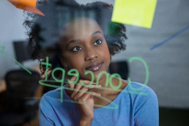 Женский графический дизайнер, глядя на стекло