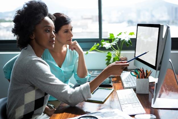 Female graphic designer pointing to desktop pc