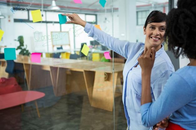 クリエイティブ・オフィスのガラスに付箋を指している女性のグラフィックデザイナー