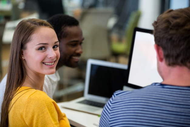 Female graphic designer smiling at camera while colleagues interacting with each other