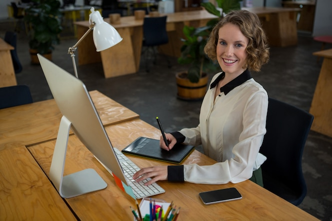 Female graphic designer smiling while using desktop pc and graphic tablet