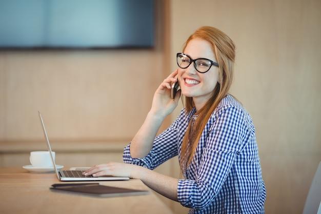 사무실에서 작업하는 동안 휴대 전화에 말하는 여성 그래픽 디자이너