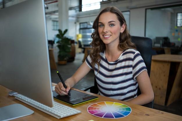 Женский графический дизайнер с помощью графического планшета на столе