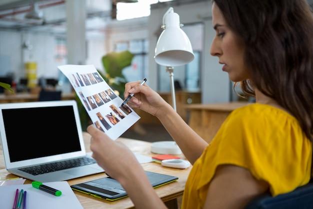 Женский графический дизайнер, работающий за столом