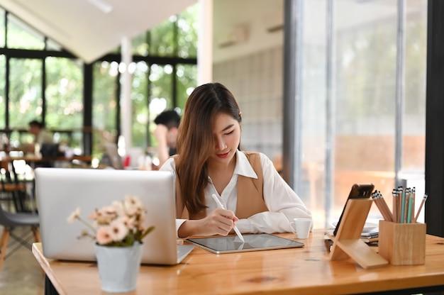 オフィスのデスクでスタイラスペンを使用しながらコンピューターのタブレットに取り組んでいる女性のグラフィックデザイナー。