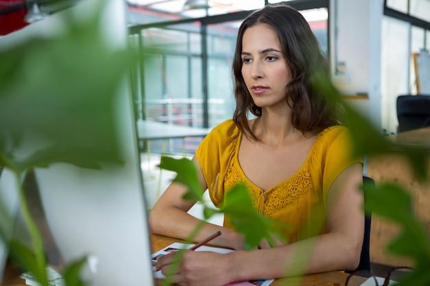 コンピューターに取り組んでいる女性のグラフィックデザイナー