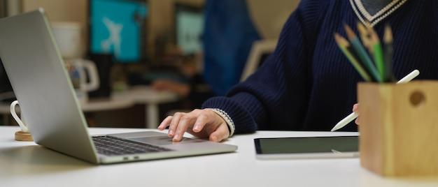 흰색 사무실 책상에 디지털 태블릿 및 노트북을 사용하는 여성 그래픽 디자이너