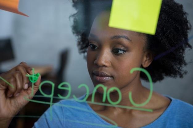 Женский графический дизайнер пишет на стекле