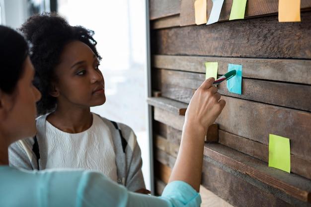 Female graphic designer writing on sticky notes