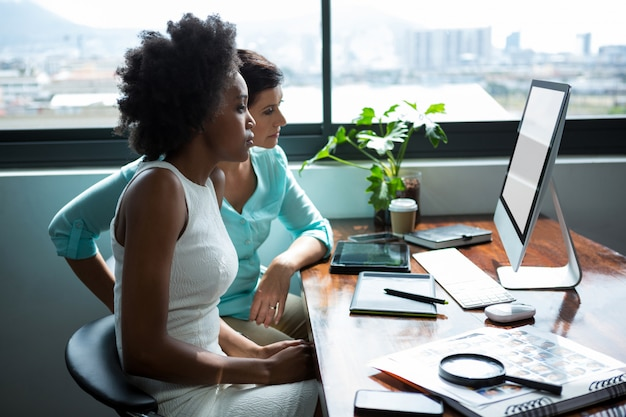 Female graphic designers looking at desktop pc