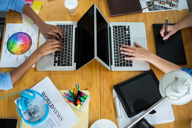 Графические дизайнеры женского пола, использующие ноутбук на столе