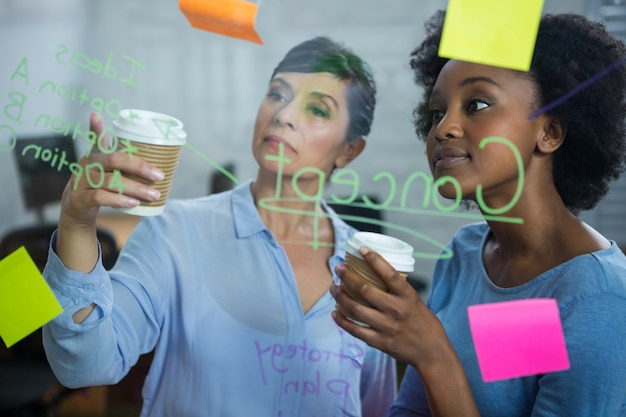 Female graphic designers with disposable cup reading text on the glass