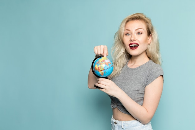 Female in grey shirt and bright blue jeans holding little globe