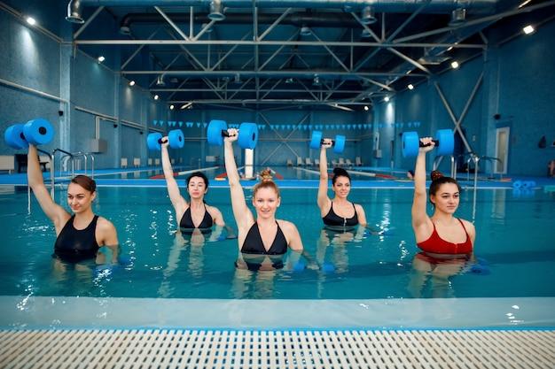 아쿠아 에어로빅을 하는 여성 그룹은 수영장에서 아령으로 운동합니다. 물 속의 여성, 스포츠 수영 피트니스 운동