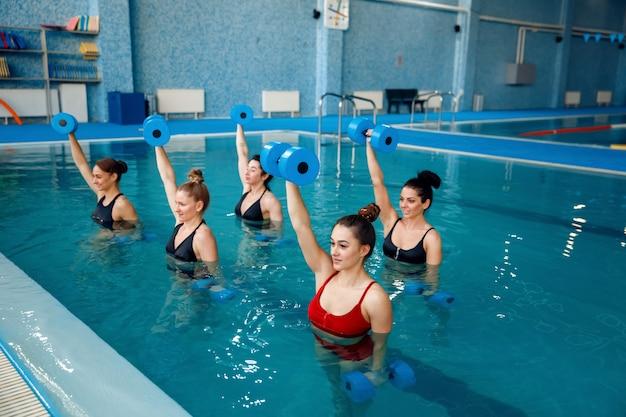 아쿠아 에어로빅을 하는 여성 그룹은 수영장에서 아령으로 운동합니다. 물 속의 여성, 스포츠 수영 피트니스