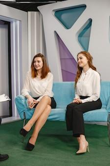 女性客がソファに座っている。取材を受けるジャーナリスト。モーニングショー。
